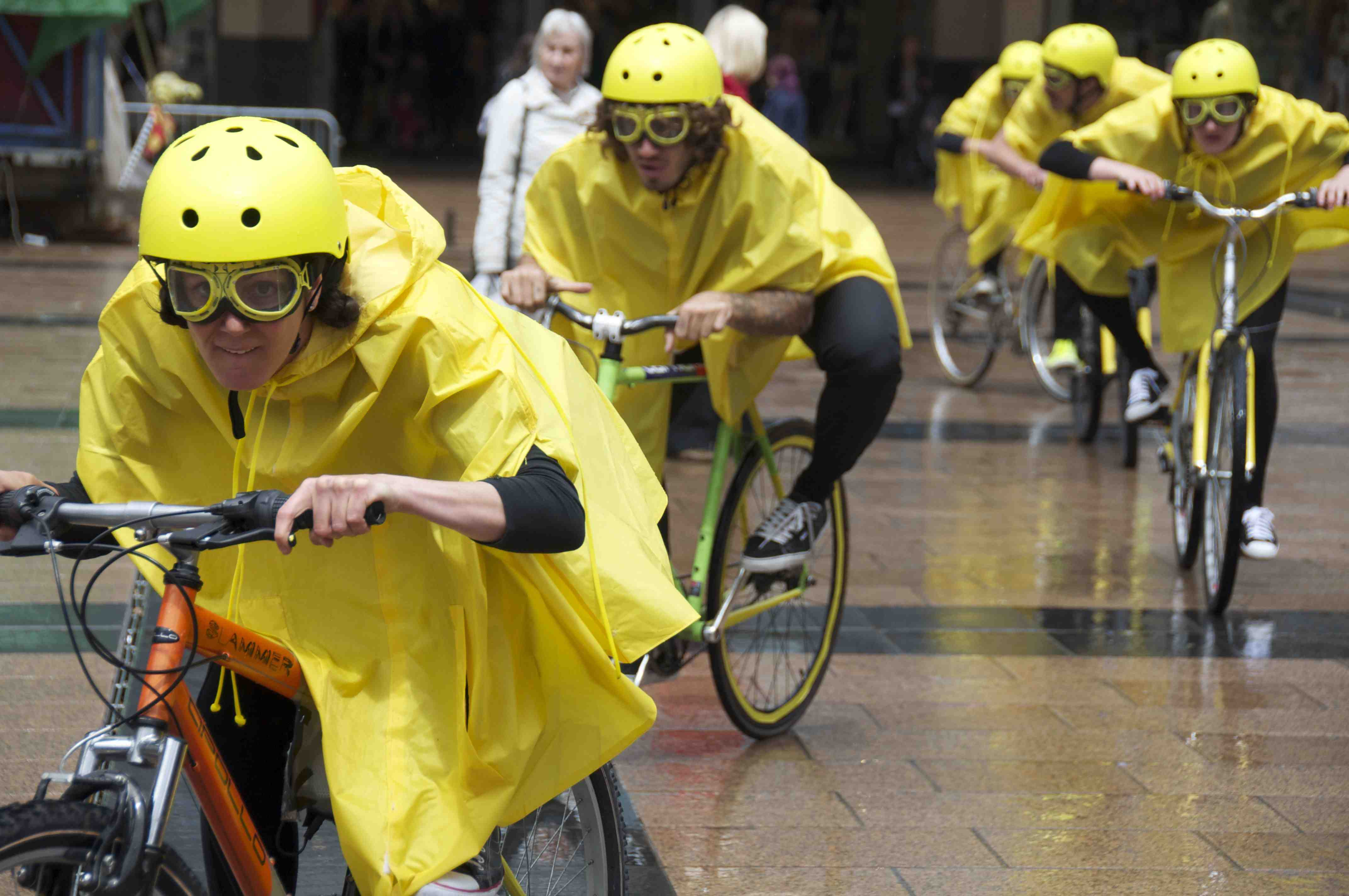 Performers in yellow rain macs, helmets and goggles hunch low over their bike handlebars cycling towards the camera