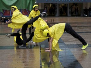 Performers in yellow rain macs, helmets and goggles cluster together forming a human installation
