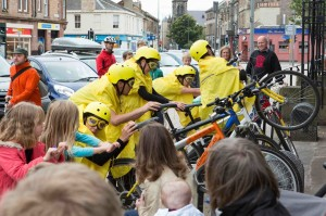 5 yellow cyclists lean over their bikes' back wheels and grab the handlebars, surrounded by people mimicking them without bikes