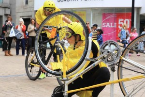 Performer in Yellow helmet, goggles & rain mac kneels behind her upside down bike, peering through the wheel