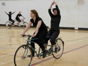 VI back riders raise their arms above their heads whilst cycling along on tandems