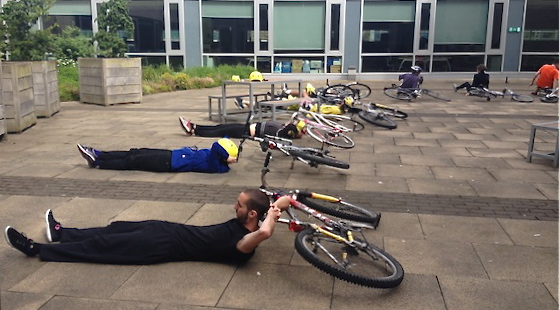 A curving line of workshop participants lie on the floor relaxing, with their heads resting on the saddles of their laid down bikes