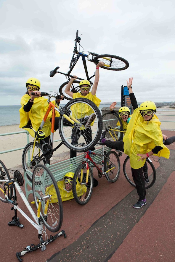 Performers in yellow costumes hold their bikes up on and underneath a bench