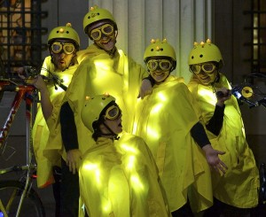 5 performers in yellow glowing capes, helmets & goggles post with a bike on each side