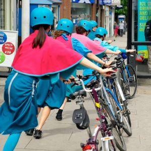 Five performers with blue helmets, skirts & bloomers, topped with bright pink capes, walk along a pavement with their bikes on the right side, each leaning in to create an arch with their bikes