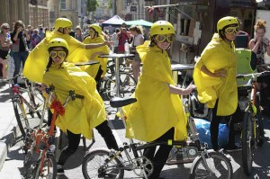 Five performers in yellow helmets, yellow goggles and yellow capes lean against their bikes around a circular table, each looking in different directions and pulling faces