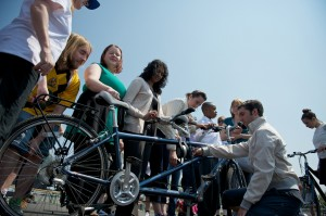 VIPs & performers crowd around a tandem to explore the bike during a Touch Tour before an Everyday Hero performance 2013 © Ray Gibson