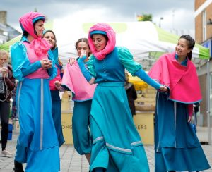 Five women dressed in bright blue & pink Edwardian-style dress, walk down a street chatting