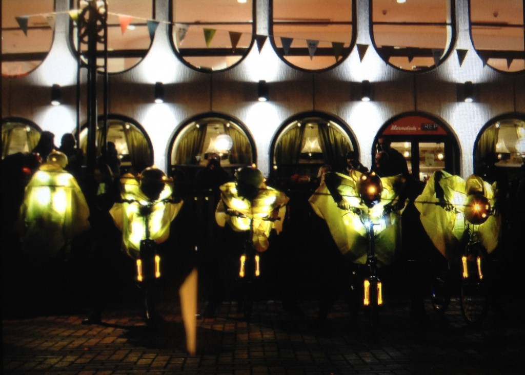 Five glowing yellow clad cyclists line up on their bikes