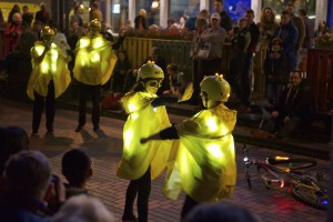 Yellow glowing performing miming being on a bike is halted by the hand from another held in front of their face