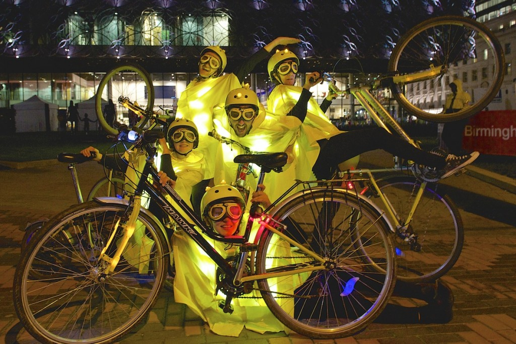 five performers in yellow capes, goggles & helmets which are lit up, pose behind a bike wheel