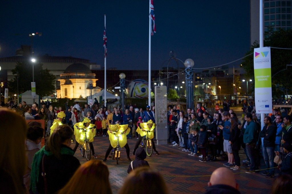 Three glowingly yellow clad performers stand astride their bikes & race towards the finish line held by two audience members, crowds look on