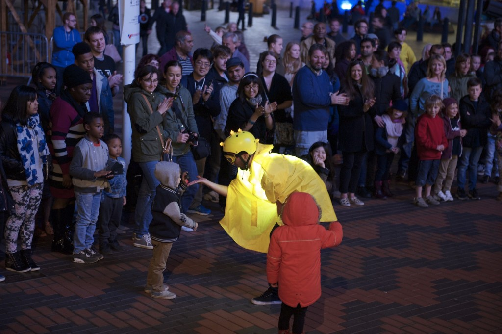 Glowing performer in yellow cape, goggles, with lights on top of helmet, bends down to thank a small boy for participating in the show