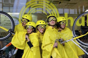 5 performers dressed in yellow rain capes, helmets & goggles huddle together looking in all directions, the outer two holding bicycle handlebars