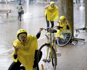 A performer dressed in yellow cape, helmet & goggles kneels on the floor next to her bicycle, berating an imaginary driver who has knocked her off her bike!